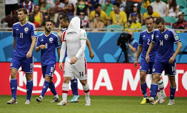 Iran's Andranik Teymourian reacts after Bosnia's Miralem Pjanic, second left, scored his side's second goal during a group F World Cup soccer match between Bosnia and Iran at the Arena Fonte Nova in Salvador, Brazil, Wednesday, June 25, 2014. (AP Photo/Fernando Llano)