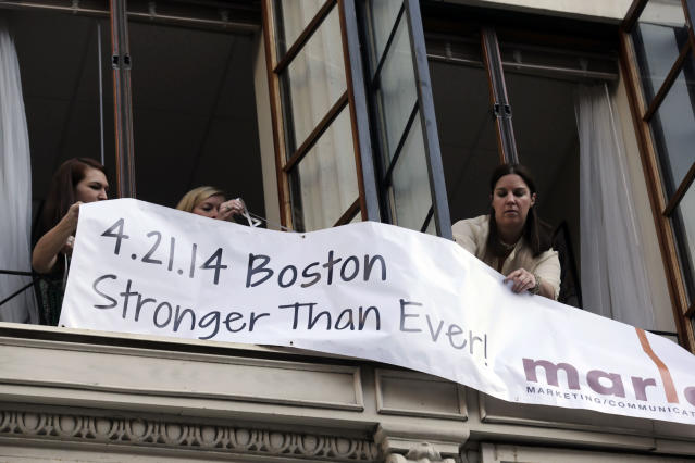 Marla Fogelman, right, hangs a banner on the second floor over Marathon Sports store, the site of the first bomb blast in 2013, before the start of the 118th Boston Marathon Monday, April 21, 2014 in Boston. (AP Photo/Charles Krupa)