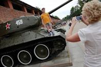 A child has his picture taken on top of a a Soviet-style tank displayed at Kremlin in Nizhny Novgorod, Russia, June 30, 2018. REUTERS/Damir Sagolj