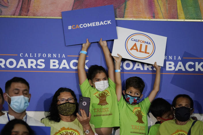 Young supporters hold signs as California Gov. Gavin Newsom speaks during a rally where Newsom would sign the California Comeback Plan relief bill Tuesday, July 13, 2021, in Los Angeles. (AP Photo/Marcio Jose Sanchez)