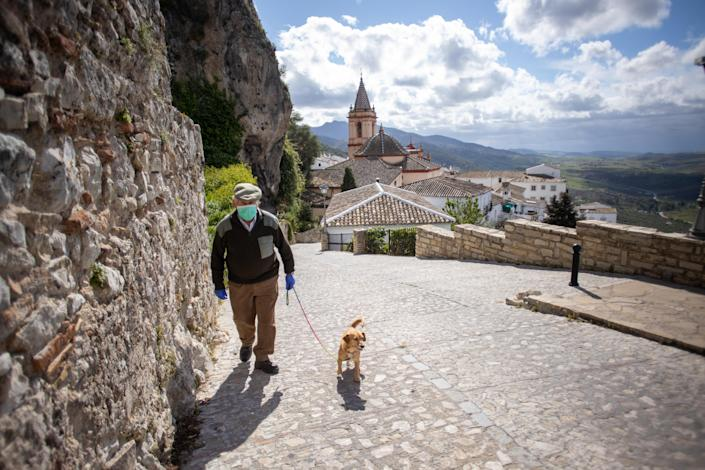 A man in a face mask walks his dog through the cobbled streets of Zahara de la Sierra, Spain. (Getty Images)