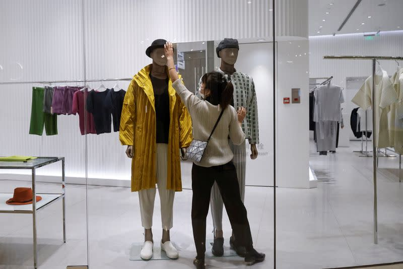 A staff member arranges the clothing on a mannequin in a boutique in a department store following an outbreak of the coronavirus disease (COVID-19) in Beijing