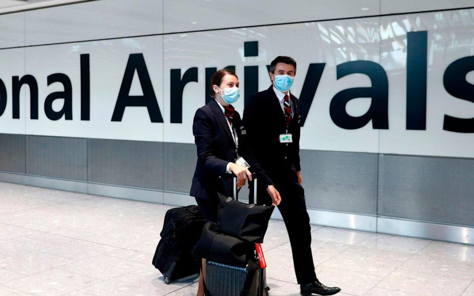 Members British Airways flight crew wear protective facemasks as they arrive at Terminal 5 at Heathrow airport in west London as the UK government's planned 14-day quarantine for international arrivals to limit the spread of Covid-19 starts on June 8, 2020. (Photo by Adrian DENNIS / AFP) (Photo by ADRIAN DENNIS/AFP via Getty Images) - Adrian DENNIS/AFP via Getty Images