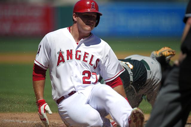 Los Angeles Angels' Mike Trout, left, is tagged out by Oakland Athletics catcher Derek Norris while trying to score on a ball hit by Josh Hamilton during the second inning of a baseball game, Sunday, Aug. 31, 2014, in Anaheim, Calif. (AP Photo/Mark J. Terrill)