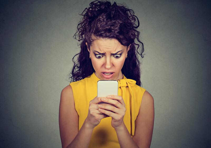Portrait anxious scared girl looking at phone seeing bad message isolated on gray wall background. Human emotions