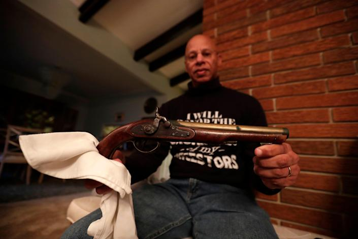 "A.J. Brickler III holds the pistol that belonged to his late relative Harriet Tubman. The Brickler family rented an entire movie theater for them and their friends to watch the recent release of ""Harriet,"" a movie depicting her life."