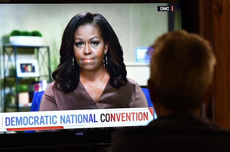 A person watches former First Lady Michelle Obama speak during the opening night of the Democratic National Convention, being held virtually amid the novel coronavirus pandemic, in Los Angeles, on August 17, 2020. - America's political convention season begins tonight with former first lady Michelle Obama addressing the Democrats' now-virtual gathering set to anoint Joe Biden, as President Donald Trump defies coronavirus concerns to rally supporters in battleground Wisconsin. (Photo by Chris Delmas / AFP) (Photo by CHRIS DELMAS/AFP via Getty Images) (Photo: CHRIS DELMAS via Getty Images)