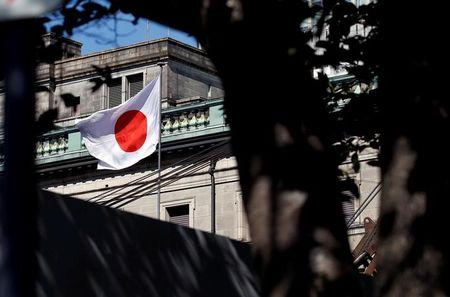 FILE PHOTO: A Japanese flag flutters atop the Bank of Japan building under construction in Tokyo