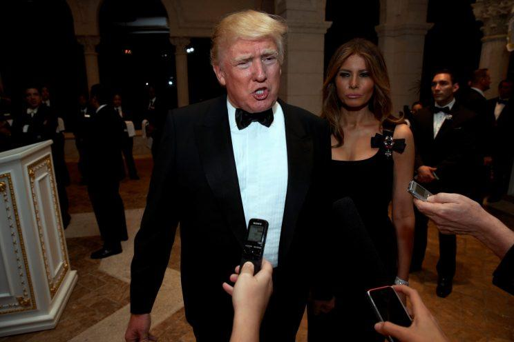 Trump talks to reporters as he and his wife, Melania Trump, arrive for a New Year's Eve celebration at Mar-a-Lago. (Jonathan Ernst/Reuters)