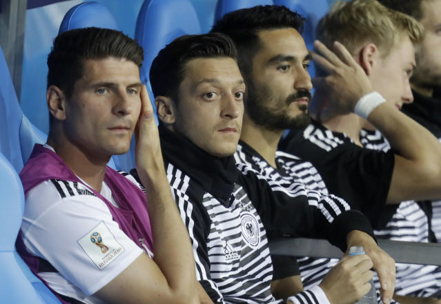 Germany's Mario Gomez, Mesut Ozil and Ilkay Gundogan, from left, sit on the bench prior to the group F match between Germany and Sweden at the 2018 soccer World Cup in the Fisht Stadium in Sochi, Russia, Saturday, June 23, 2018. (AP Photo/Michael Probst)