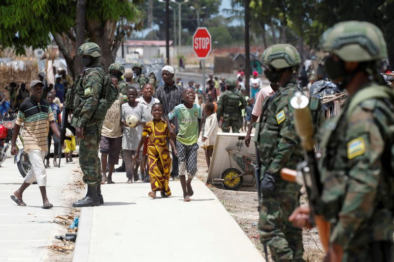 Children walk past Rwandan security forces soldiers in camp for internally displaced in Quitunda