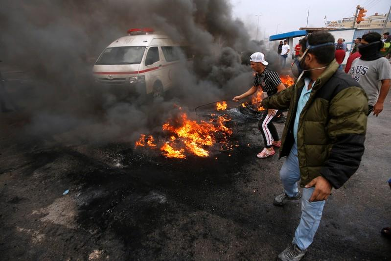 Iraqi protesters burn tires during the ongoing anti-government protests in Basra
