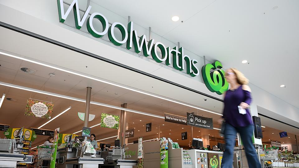 A woman walks past the front of a Woolworths store in Sydney.