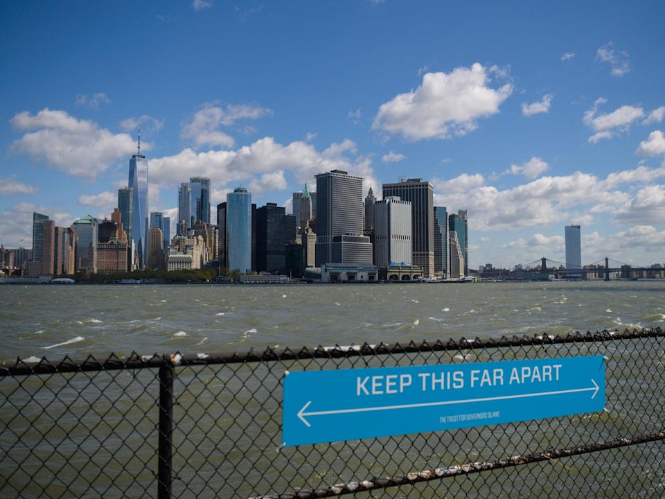 In this file photo a sign to promote social distancing is seen on Governors Island on 30 April 2021 in New York City (AFP via Getty Images)