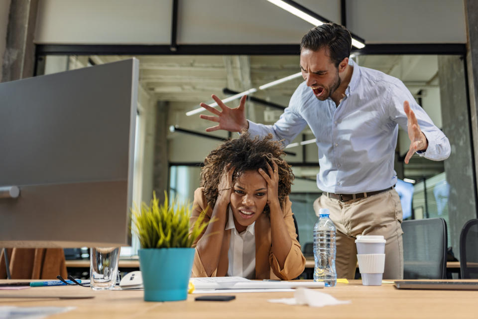 Male and female Office employees having argument at workplace.