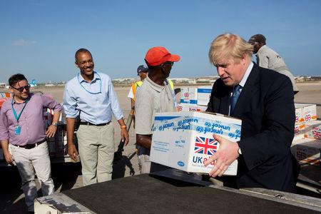 Britain's Foreign Secretary Boris Johnson helps to load supplies for treating malnourished children affected by the severe drought in Somalia onto a cargo plane at Mogadishu International Airport in Mogadishu