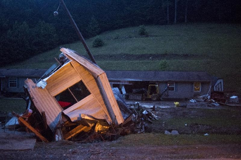 A mobile home lies on its side off the road in front of a home after it was washed away by a flash flood along Jordan Creekon in Elkview, West Virginia on June 25, 2016 (AFP Photo/Ty Wright)