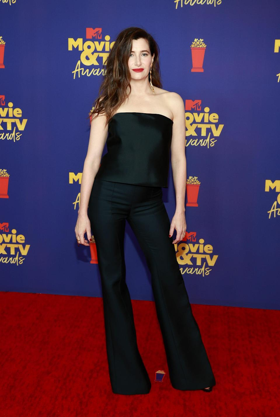 Nothing screams classy like a matching pant suit. <em>WandaVision</em> actor Kathryn Hahn kept it simple in a satin tube top and flared pants with a bold red lip and gold earrings to accessorize.