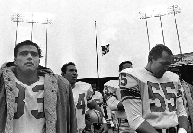 FILE - In this Nov. 24, 1963, file photo, Detroit Lions' Nick Pietrosante, left, and Wayne Walker (55) stand during ceremonies honoring slain President John F. Kennedy before an NFL football game against the Minnesota Vikings at Metropolitian Stadium in Minneapolis. Americans grieved in front of their televisions on a brutally grim Sunday afternoon 50 years ago as a horse-drawn caisson took the body of President Kennedy to lie in state in the Capitol rotunda. As unimaginable as it might seem today, in seven cities men played football as the NFL went on despite the assassination two days earlier. (AP Photo/File)