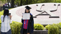 Recent University of Akron graduate Sulochana Shrestha, right, poses for a photo taken by her sister, Sushma, on campus, Thursday, May 13, 2021, in Akron, Ohio. Ohio Gov. Mike DeWine recently announced a weekly $1 million prize and full-ride college scholarships to entice more Ohioans to get the COVID-19 vaccine. (AP Photo/Tony Dejak)