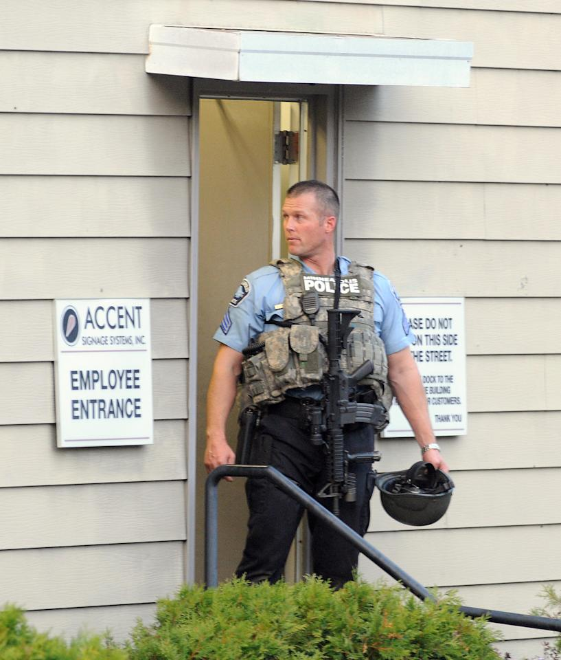 A Minneapolis police officer stands at the entrance of Accent Signage Systems as police investigate the scene of a business in which a gunman reportedly shot several people and then turned the gun on himself, about 4:30 p.m. in the Bryn Mawr neighborhood of Minneapolis, Thursday, Sept. 27, 2012. (AP Photo/Craig Lassig)