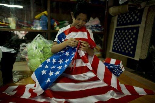A local woman is seen folding US national flags at a shop in Yangon. The United States on Friday lifted a nearly decade-old ban on most imports from Myanmar, saying it was hoping to encourage recent reforms days before a landmark visit by President Barack Obama