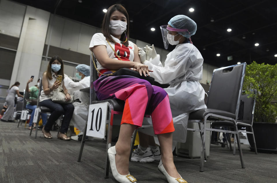 Health workers administer a dose of the AstraZeneca COVID-19 vaccine to women at Paragon shopping mall in Bangkok, Thailand, Monday, June 7, 2021. Health authorities in Thailand on Monday began their much-anticipated mass rollout of locally produced AstraZeneca vaccine, but it appeared that supplies were falling short of demand from patients who had scheduled vaccinations for this week. (AP Photo/Sakchai Lalit)