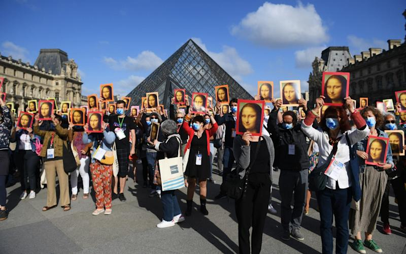 Visitors hold reproductions of the Mona Lisa outside the museum  - Getty Images Europe