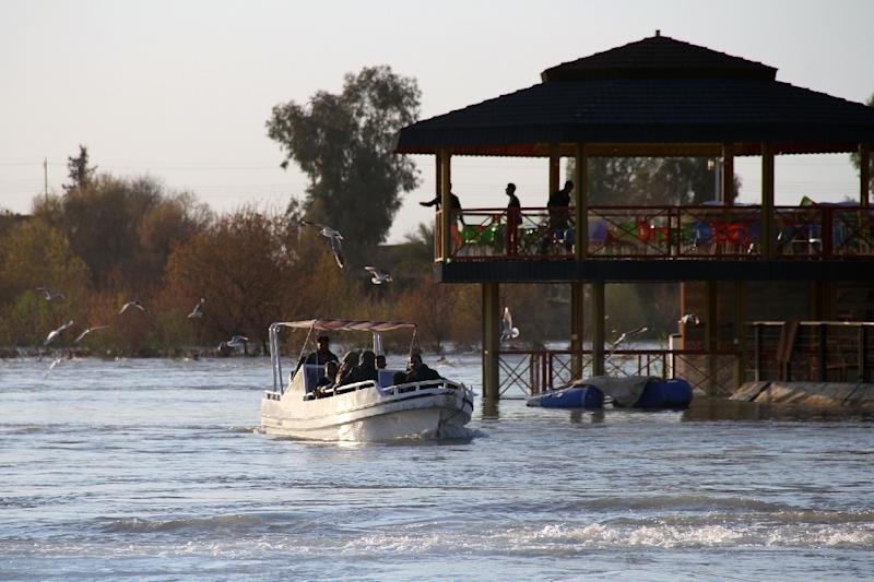 A boat passes the site of a popular Mosul picnic area near where the ferry sank on Thursday (AFP Photo/Waleed AL-KHALED)