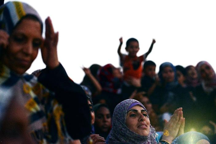 A Palestinian woman joins others in clapping and cheering during a wedding ceremony at a UN school school in Gaza City's Shati refugee camp on August 13, 2014 (AFP Photo/Roberto Schmidt)