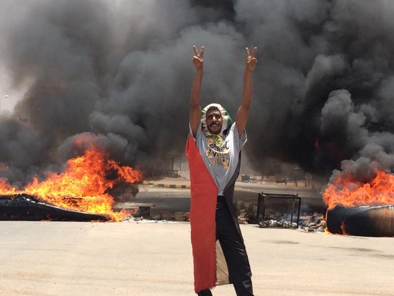 FILE - In this June 3, 2019 file photo, a protester flashes the victory sign near the army headquarters, in Khartoum, Sudan. Late Saturday, Sept. 21, 2019, Prime Minister Abdalla Hamdok said that Sudan is launching an independent investigation into the deadly crackdown on protesters earlier in June. According to the protesters, at least 128 people were killed and hundreds wounded when security forces violently dispersed the protesters' main sit-in outside the military headquarters in the capital, Khartoum, on June 3. Authorities put the death toll at 87, including 17 inside the sit-in area. (AP Photo, File)