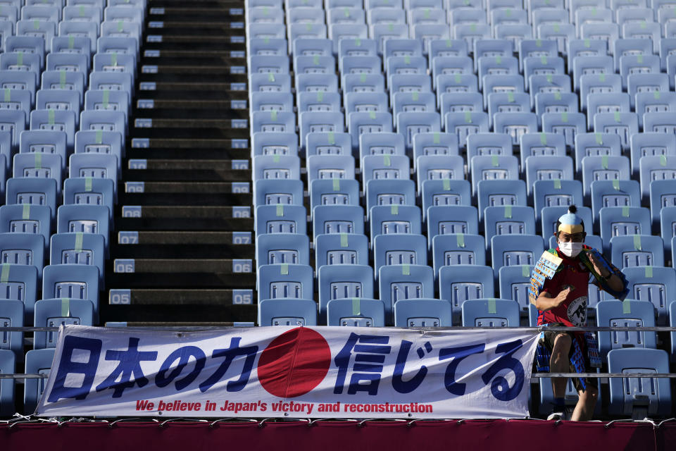 A fan poses for poses for a picture as he arrives at Miyagi Stadium for a women's soccer match at the 2020 Summer Olympics, Saturday, July 24, 2021, in Miyagi, Japan. (AP Photo/Andre Penner)