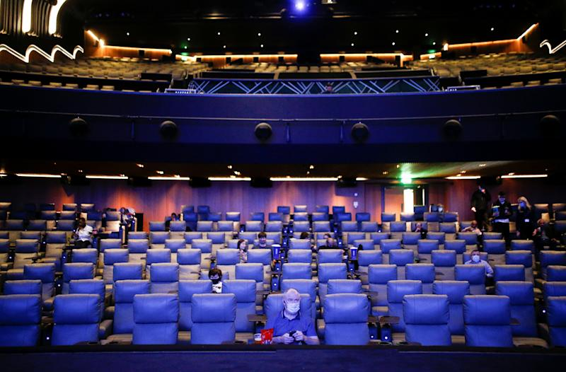 """People take their seats inside the Odeon Luxe Leicester Square cinema, on the opening day of the film """"Tenet"""", amid the coronavirus disease (COVID-19) outbreak, in London, Britain, August 26, 2020. REUTERS/Henry Nicholls"""