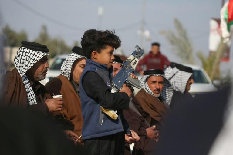 An Iraqi child carries a mock machine gun as armed members of Karbala clans take to the streets to declare their support for the Iraqi armed forces