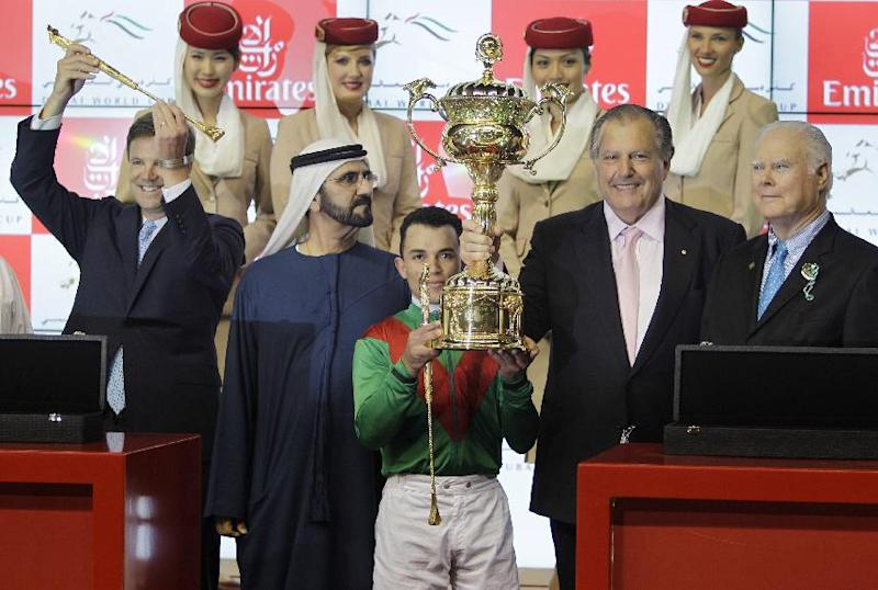 Joel Rosario, centre, jockey of Animal Kingdom of U.S., holds the trophy after he wins the US dollars 6,000,000 (4,679,275 euro) 1st place prize of Dubai World Cup at Meydan racecourse in Dubai, United Arab Emirates, Saturday, March 30, 2013. From left to right, American trainer Graham Motion, Sheikh Mohammed bin Rashid Al Maktoum, UAE prime minister and ruler of Dubai, Australian owner John Messara and an unidentified person are present on the podium. (AP Photo/Kamran Jebreili)