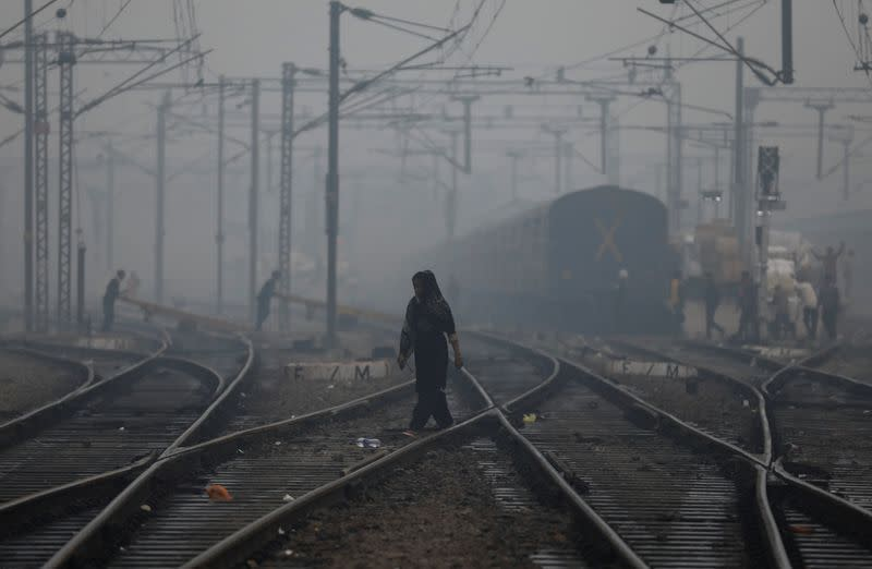 FILE PHOTO: A woman crosses a railway line on a smoggy morning in New Delhi