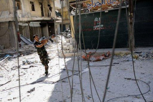 A Syrian rebel aims his weapon as he tries to dodge pro-government sniper fire in Aleppo