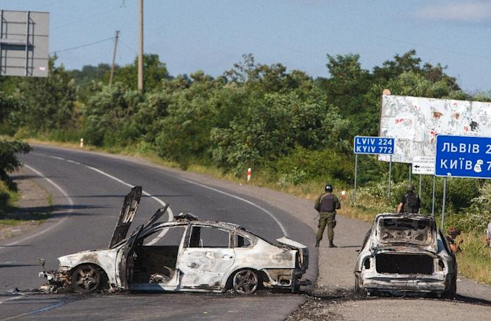 Servicemen stand next to burnt cars in Mukacheve, southwestern Ukraine on July 11, 2015, where at least two people were killed and several more injured in fighting between police and heavily armed members of ultranationalist Pravy Sektor movement (AFP Photo/Alexander Zobin)