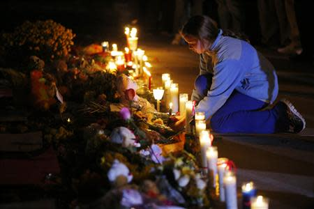 A girl lights a candle at a makeshift memorial for teacher Colleen Ritzer outside the high school where she taught in Danvers, Massachusetts October 23, 2013. REUTERS/Brian Snyder
