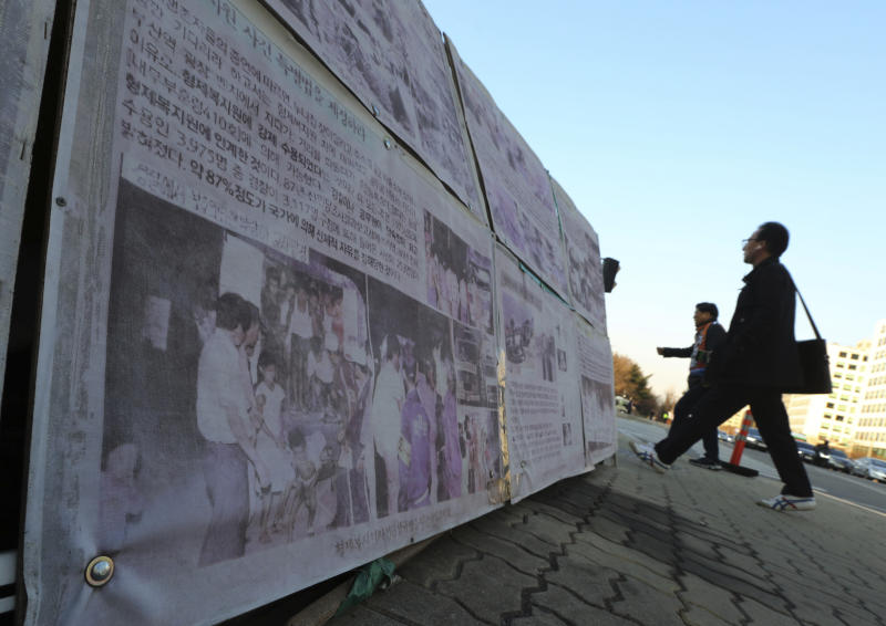 In this April 2, 2019, photo,  people walk past a photo of guards unloading children from a truck at the Brothers Home in Busan, as it is displayed in front of National Assembly in Seoul, South Korea. A notorious South Korean facility that kidnapped, abused and enslaved children, adults and the disabled for a generation was also shipping children overseas for adoption, part of a massive profit-seeking enterprise that thrived by exploiting those trapped within its walls, The Associated Press has found.(AP Photo/Ahn Young-joon)