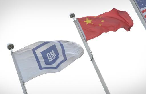 General Motors (L) and China flags fly at its China headquarters in Shanghai on April 19, 2013