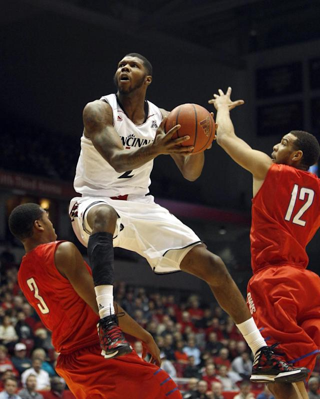Cincinnati forward Titus Rubles (2) goes up for a shot against SMU guards Sterling Brown (3) and Nick Russell (12) during the first half of an NCAA college basketball game, Wednesday, Jan. 1, 2014, in Cincinnati. (AP Photo/David Kohl)