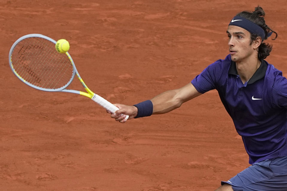 Italy's Lorenzo Musetti plays a return to Serbia's Novak Djokovic during their fourth round match on day 9, of the French Open tennis tournament at Roland Garros in Paris, France, Monday, June 7, 2021. (AP Photo/Michel Euler)