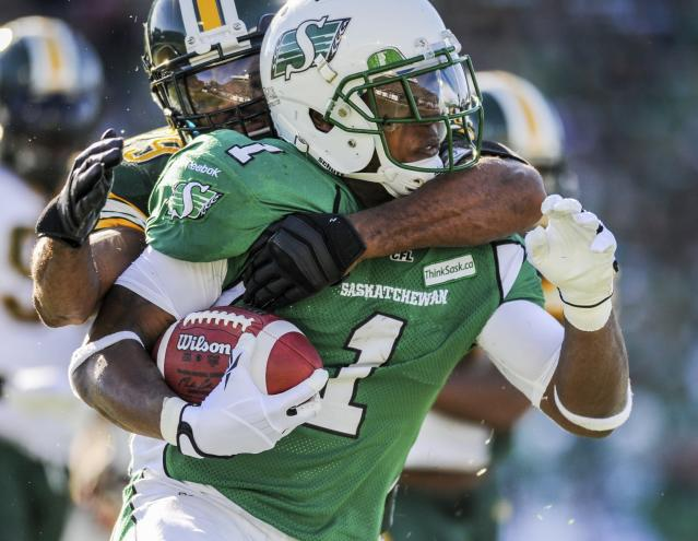Saskatchewan Roughriders running back Kory Sheets (front) is brought down by Edmonton Eskimos defensive back Chris Thompson during the first half of their CFL football game in Regina, Saskatchewan October 12, 2013. REUTERS/Matt Smith (CANADA - Tags: SPORT FOOTBALL)