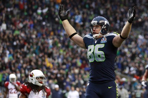 Seattle Seahawks tight end Zach Miller (86) celebrates in front of Arizona Cardinals strong safety Rashad Johnson (49) after scoring on a 24-yard touchdown reception during the second quarter of an NFL football game in Seattle, Sunday, Dec. 9, 2012. (AP Photo/Stephen Brashear)
