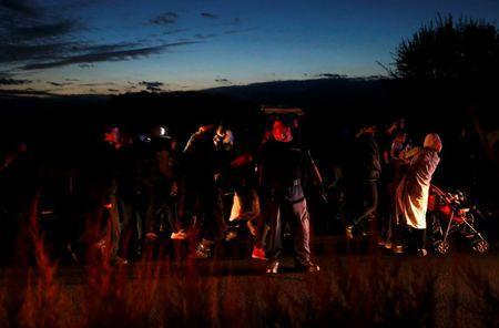 Hungarian police escorts a group of migrants walking against the traffic on a motorway leading to Budapest as they left a transit camp in the village of Roszke, Hungary, September 7, 2015. REUTERS/Laszlo Balogh