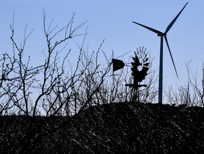 An Aermotor windmill is obscured by mesquite as a wind turbine turns in the background in south Taylor County, Texas on Jan. 15, 2021.