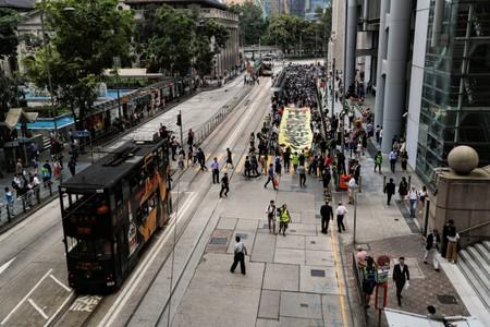 People carry a banner as they march to protest against what they say is the abuse of pro-democracy protesters by Hong Kong police, near Chater Garden in Central district, Hong Kong