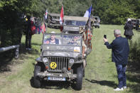 People parade in WWII vehicles in Colleville-Montgomery,, Normandy, Saturday June, 5 2021 on the eve of 77th anniversary of the assault that helped bring an end to World War II.. While France is planning to open up to vaccinated visitors starting next week, that comes too late for the D-Day anniversary. So for the second year in a row, most public commemoration events have been cancelled. A few solemn ceremonies have been maintained, in the presence of dignitaries and a few guests only. (AP Photo/David Vincent)