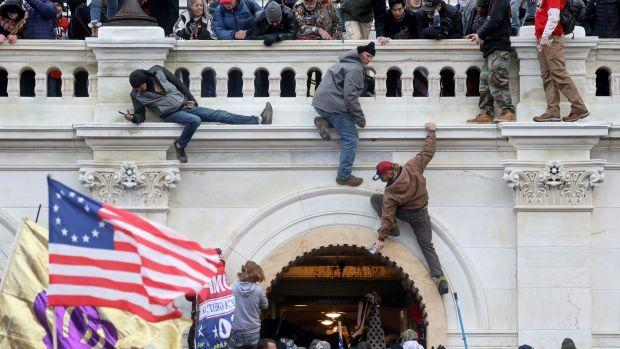 Trump supporters scale the walls of the US capitol building